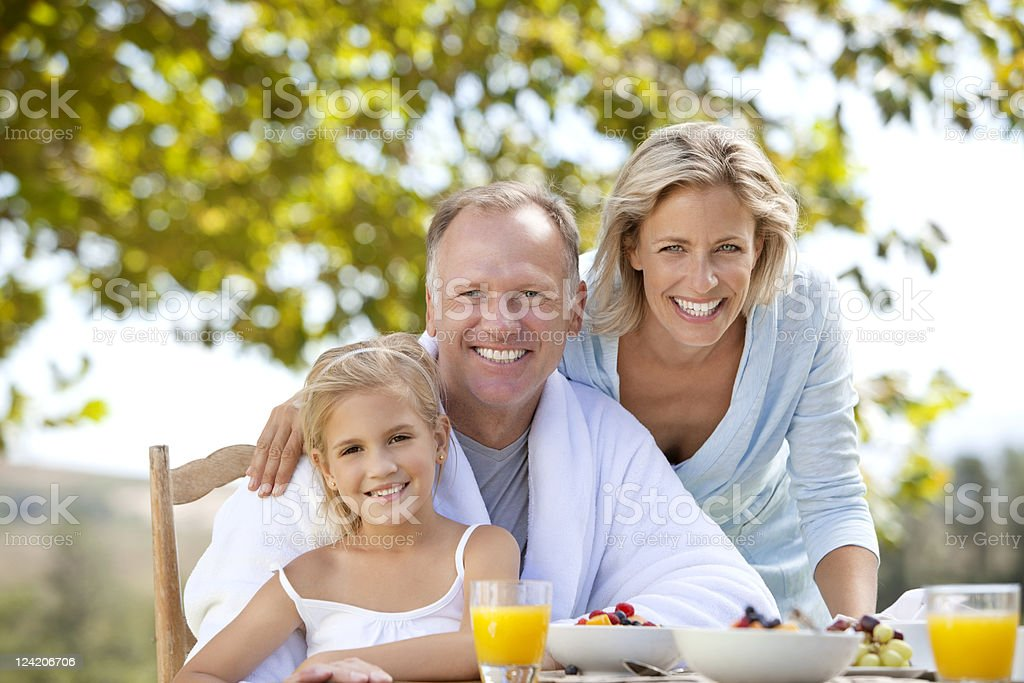 Portrait of smiling mature couple bonding with grand daughter over breakfast in lawn stock photo