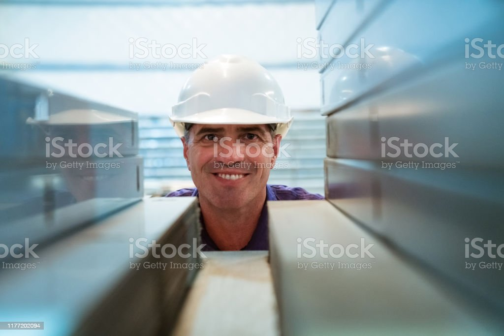 Portrait of smiling mature inspector in factory Smiling manager inspecting industrial equipment on shelf. Portrait of Inspector is on visit in manufacturing industry. He is wearing hardhat. 55-59 Years Stock Photo
