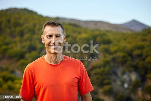 Portrait of smiling mature man. Happy male is wearing casuals. He is enjoying nature.