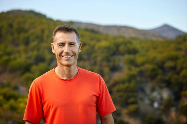 Porträt eines lächelnden reifen Mannes gegen den Berg – Foto