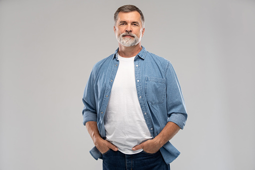 Portrait of smiling mature man standing on white background