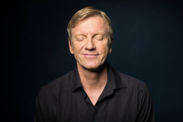 Portrait Of Smiling Mature Man With Closed Eyes stock photo