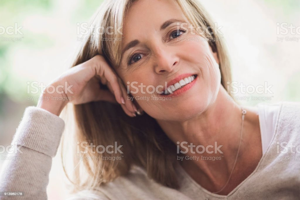 Portrait of smiling mature woman leaning on hand stock photo