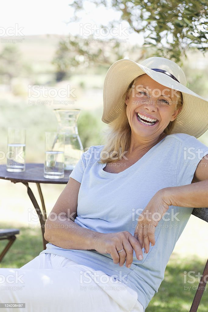 Portrait of smiling mature woman sitting in chair at the lawn royalty-free stock photo