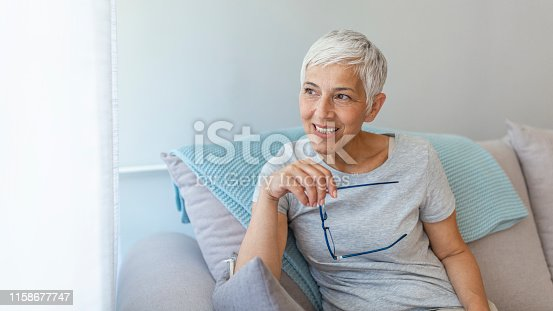 1044149594 istock photo Portrait of smiling mature woman sitting on sofa at home 1158677747