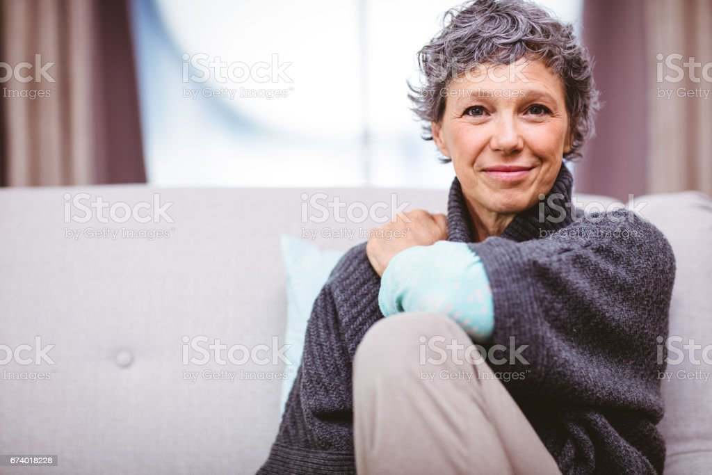 Portrait of smiling mature woman sitting on sofa stock photo