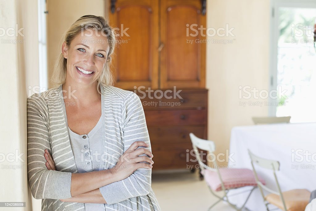 Portrait of smiling mature woman standing in living room stock photo