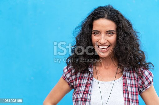 Portrait of smiling brown haired woman on blue background. Senior woman relaxing