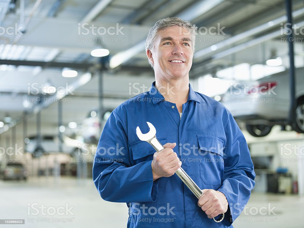 Portrait of smiling mechanic holding large wrench in auto repair shop royalty-free stock photo