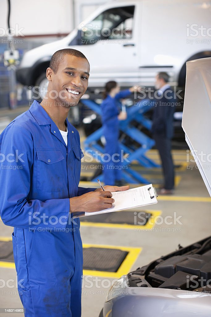 Portrait of smiling mechanic with clipboard in auto repair shop royalty-free stock photo