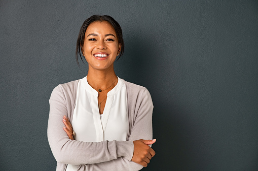 Beautiful mid adult african american woman standing on grey wall with crossed arms. Mature indian woman isolated on gray background. Portrait of smiling hispanic lady looking at camera with satisfaction.