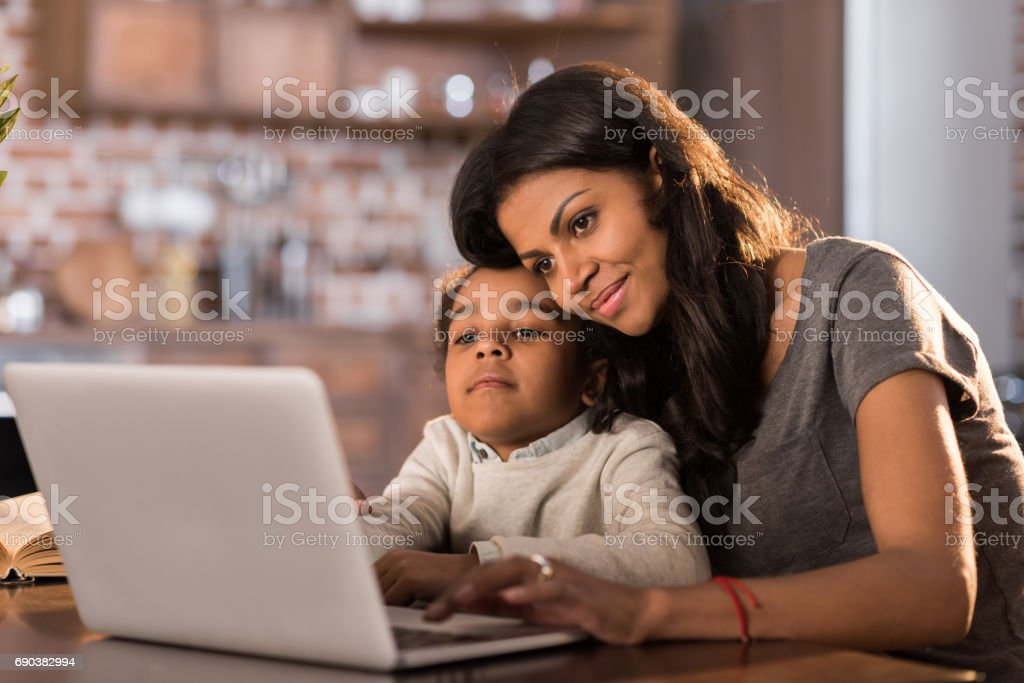 portrait of smiling mother and daughter using laptop at home stock photo