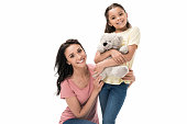 portrait of smiling mother and little daughter with teddy bear looking at camera isolated on white