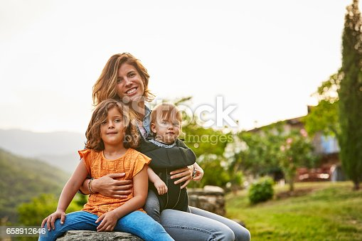 istock Portrait of smiling mother carrying kids at yard 658912646