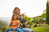 Portrait of smiling mother carrying kids at yard