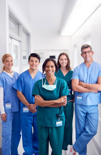 站在醫院走廊上微笑的多元文化醫療隊的肖像 - 垂直構圖 個照片及圖片檔