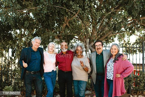 Portrait of smiling multi-ethnic senior friends standing against trees. Retired men and women are in casuals. They are at enjoying at party.