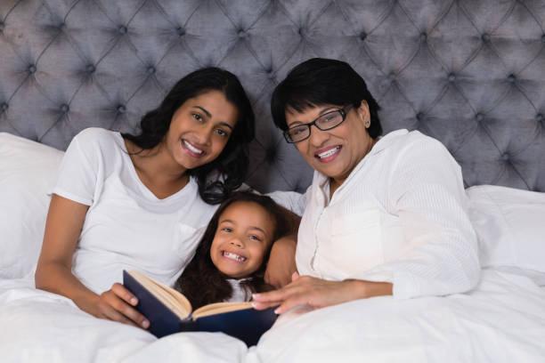 porträt des lächelns multi-generationen-familie mit buch ruht auf bett - kurzgeschichten stock-fotos und bilder