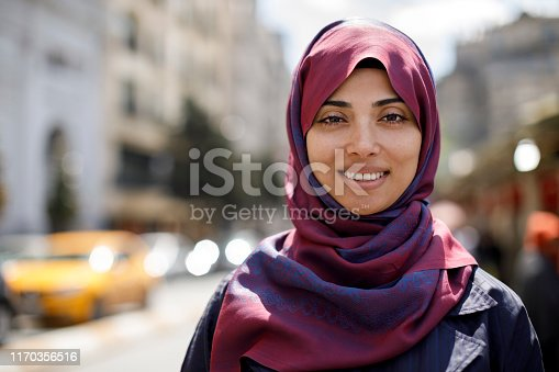 Portrait of smiling muslim woman in the city