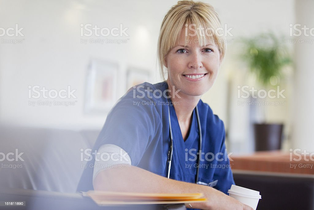 Portrait of smiling nurse drinking coffee in hospital stock photo