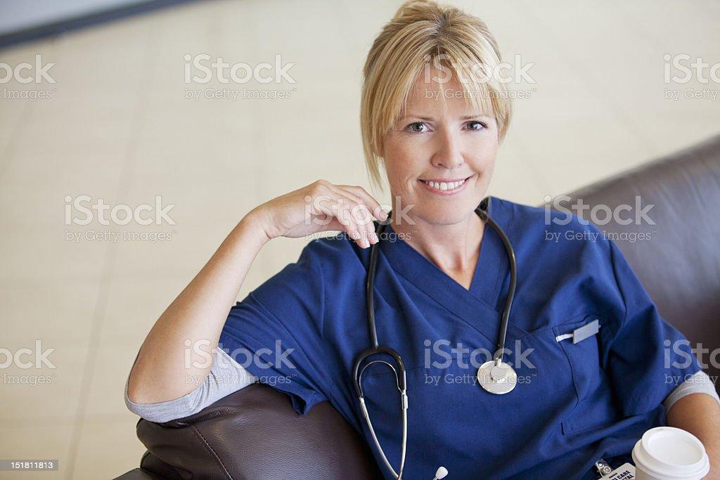 Portrait of smiling nurse drinking coffee royalty-free stock photo
