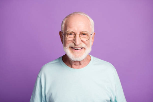 Portrait of smiling optimistic beard pensioner man wear light blue t-shirt eyeglasses isolated on purple color background stock photo