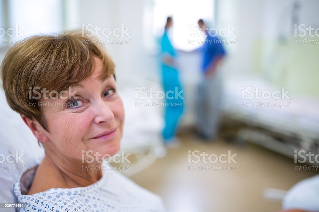 Portrait of smiling patient sitting on bed - foto de stock