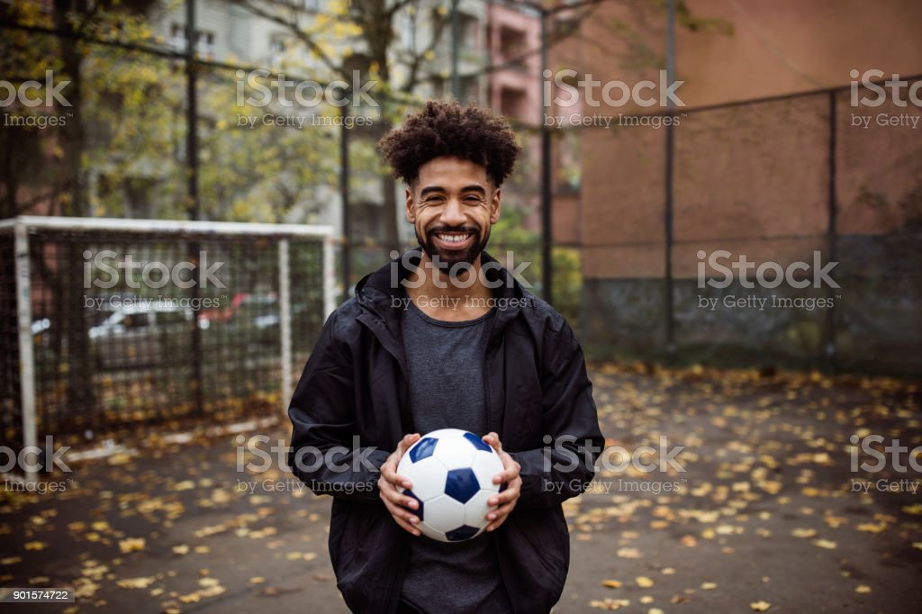 Portrait of smiling player holding soccer ball royalty-free stock photo