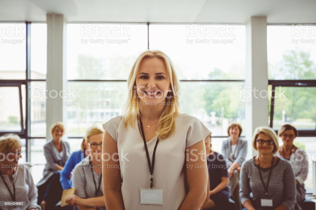 Portrait of smiling presenter with female audience in background Portrait of smiling presenter with female audience in background. Beautiful businesswoman smiling at camera. Adult Stock Photo