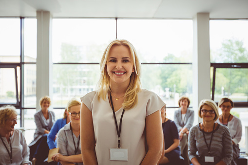 Portrait Of Smiling Presenter With Female Audience In Background Stock Photo - Download Image Now