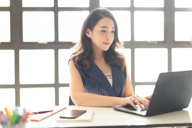 彼女のワークステーションでラップトップ上で働いているかわいい若いアジアのビジネス女性の笑顔の肖像。 - 女性 ストックフォトと画像