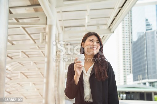 519052198 istock photo Portrait of smiling pretty young business woman in black jacket holding coffee cup 1182882199