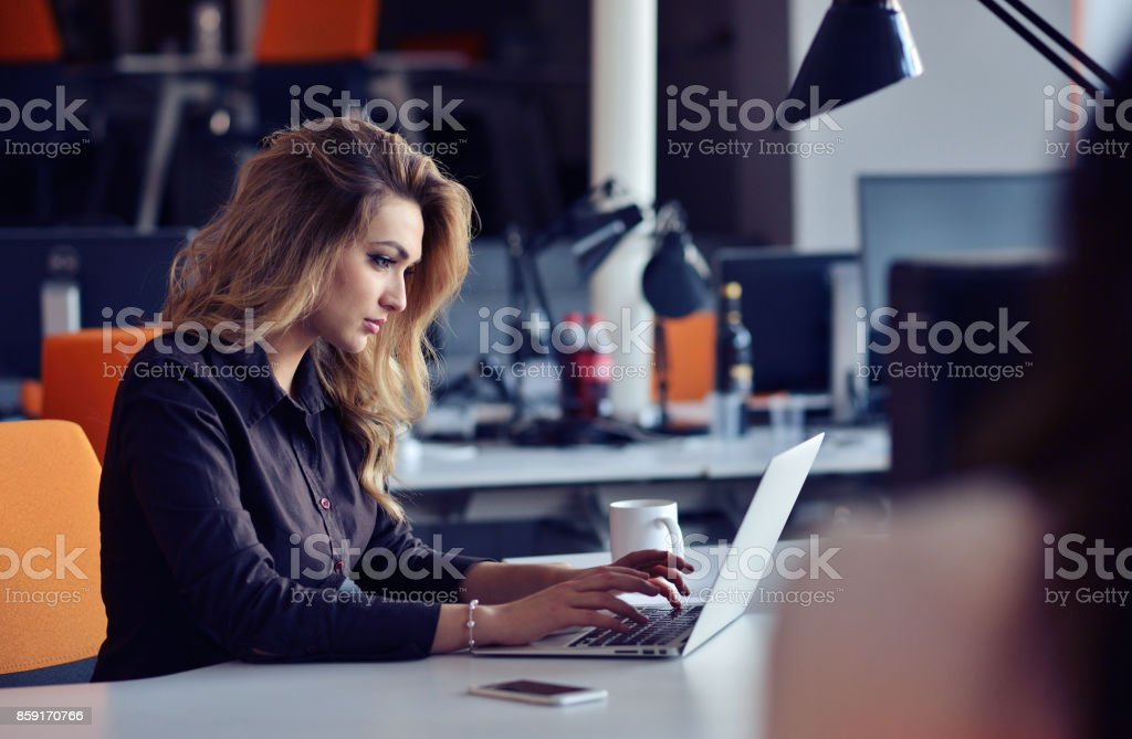 Portrait of smiling pretty young business woman sitting on workplace - Royalty-free Adult Stock Photo