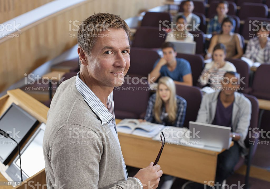 Portrait of smiling professor at podium with university students in background stock photo