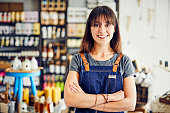 istock Portrait of smiling saleswoman standing arms crossed in deli 852208144