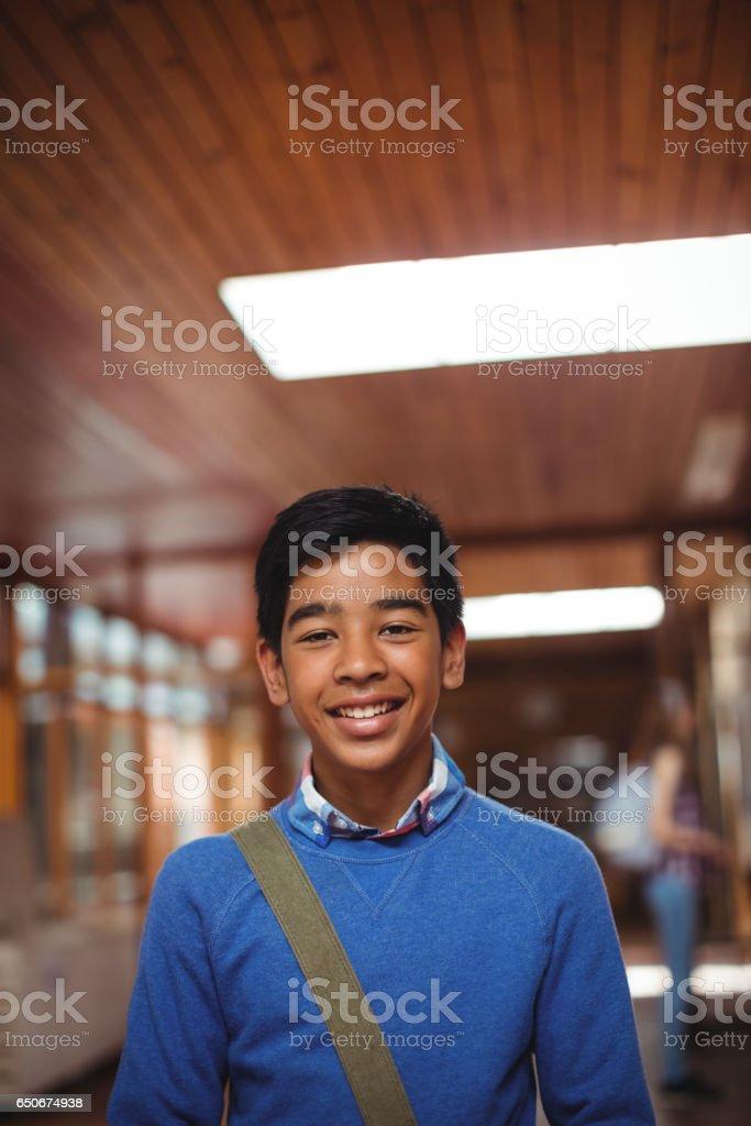 Portrait of smiling schoolboy standing in corridor stock photo