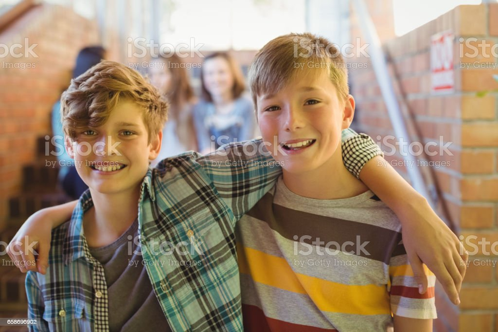 Portrait of smiling schoolboys standing with arm around in corridor royalty-free stock photo