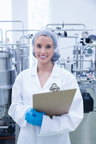 Portrait of smiling scientist holding a clipboard Portrait of a smiling scientist holding a clipboard in the factory hair net stock pictures, royalty-free photos & images