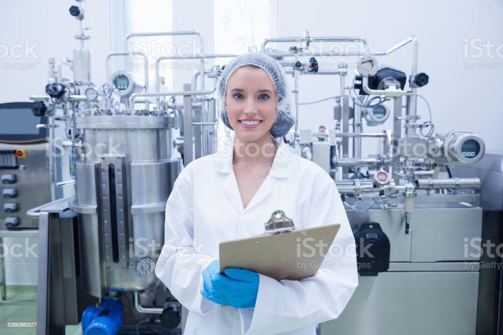 Portrait of smiling scientist holding clipboard stock photo