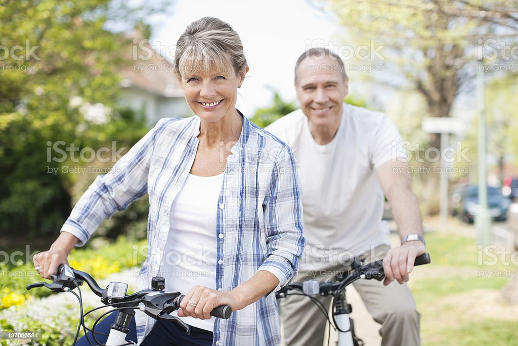 Portrait of smiling senior couple on bicycles stock photo