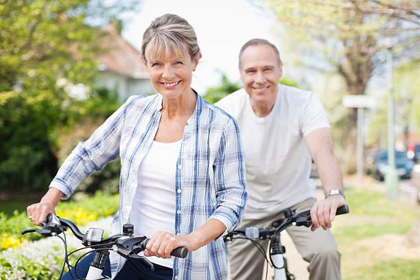 portrait of smiling senior couple on bicycles - vrouw 60 stockfoto's en -beelden