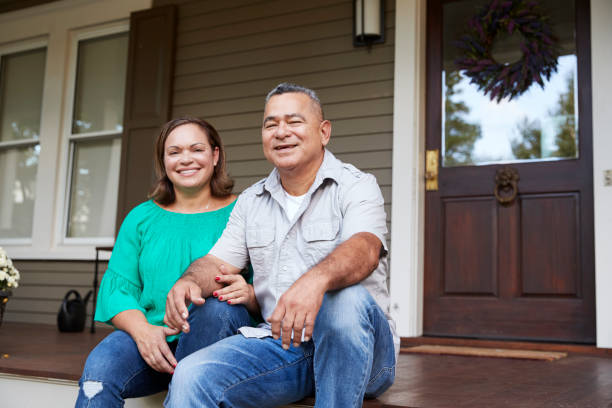 portrait of smiling senior couple sitting in front of their home - senior housing stock photos and pictures