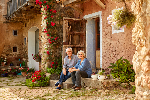 Portrait of smiling senior couple sitting on porch