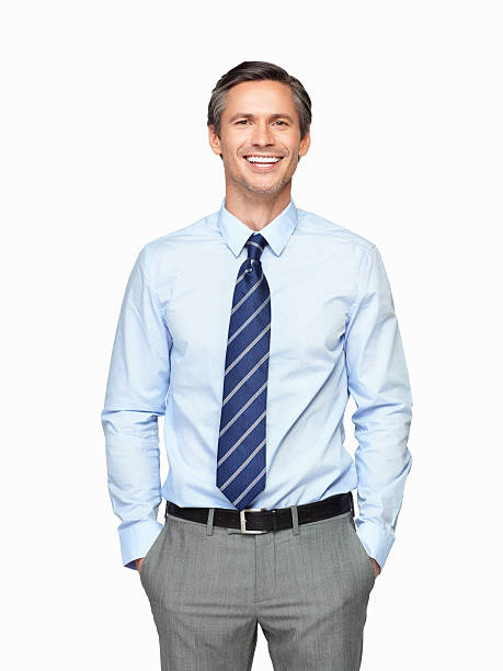 Portrait of smiling senior executive with hands in pockets stock photo