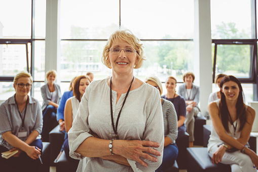 Portrait Of Smiling Senior Female Presenter With Audience In Background Stock Photo - Download Image Now
