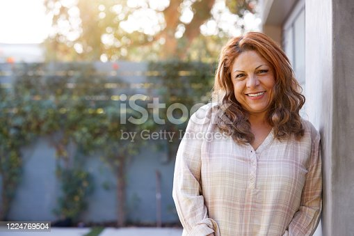 Portrait Of Smiling Senior Hispanic Woman In Garden At Home Against Flaring Sun