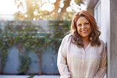 istock Portrait Of Smiling Senior Hispanic Woman In Garden At Home Against Flaring Sun 1224769504