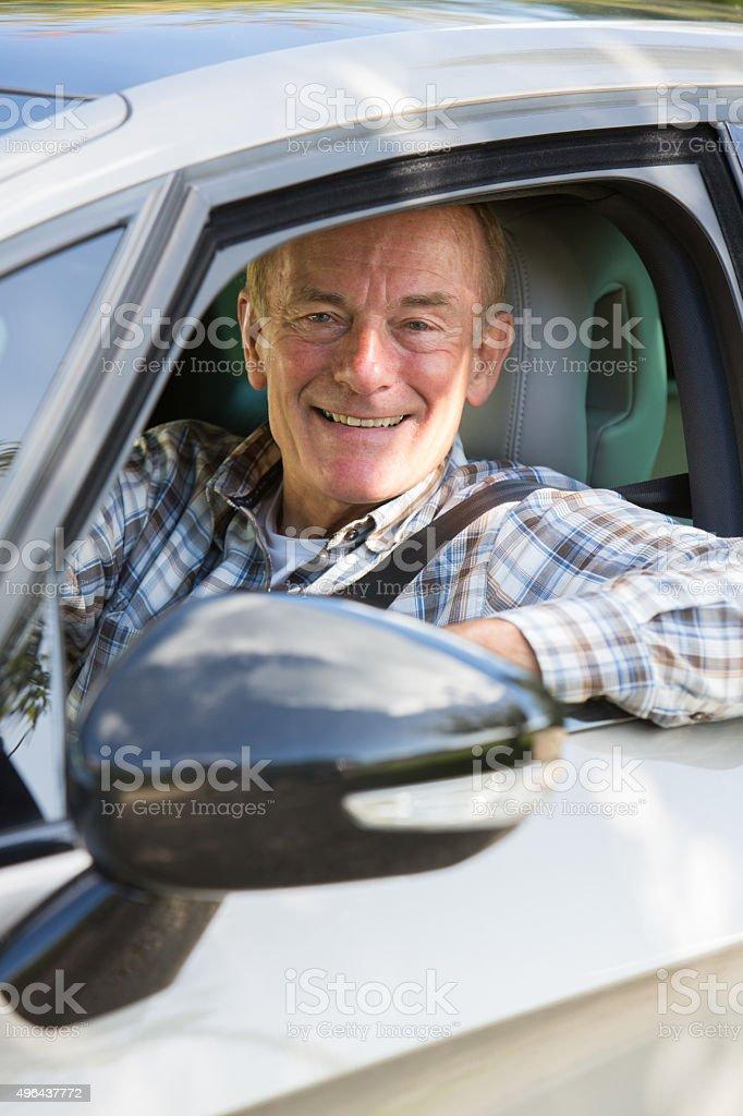 Portrait Of Smiling Senior Man Driving Car stock photo