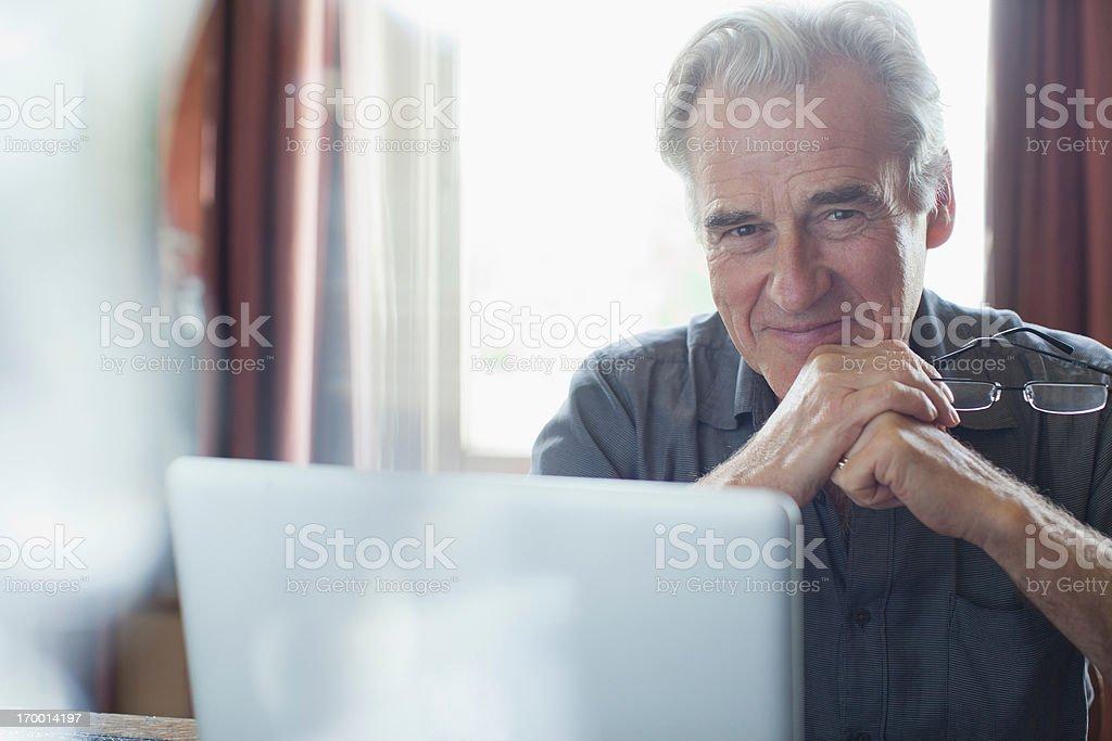 Portrait of smiling senior man holding eyeglasses and using laptop stock photo