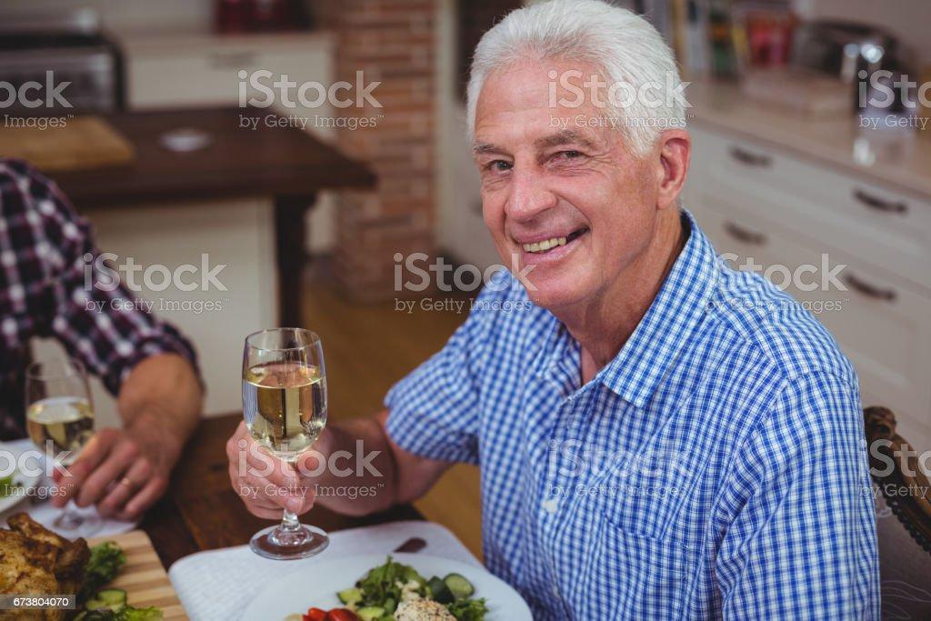Portrait d'un homme senior souriant, tenant le vin blanc photo libre de droits